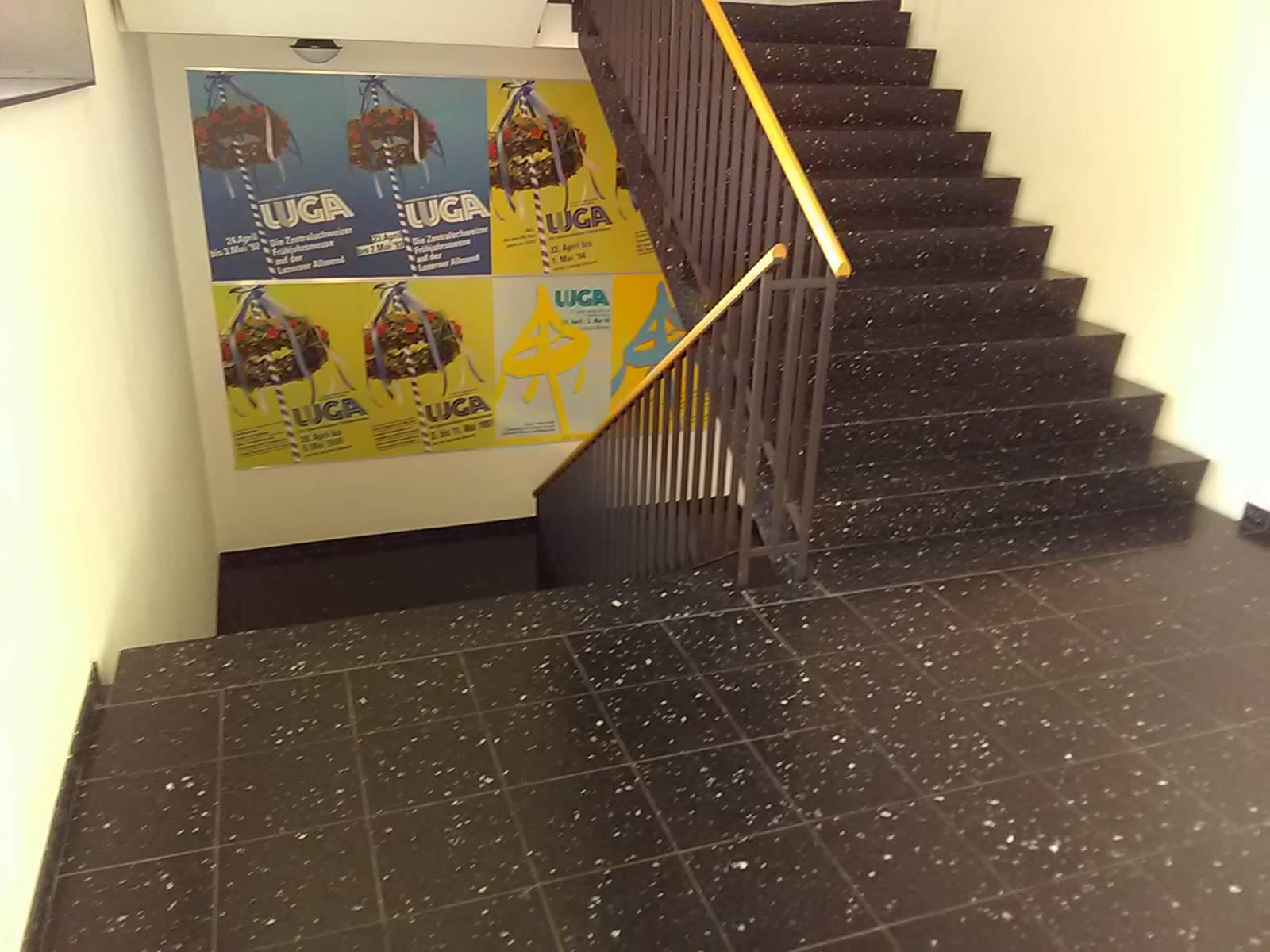 Treppen in einer Messe- und Veranstaltungshalle mit nur einseitigem Handlauf (Geländer). Beidseitig wäre notwendig
