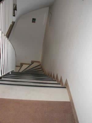 Aufgang zu einer Arztpraxis, öffentlich zugänglich, mühsam plagen sich die Patienten auf den schmalen Stufen und dem inneren Geländer nach oben. Gem. Bauordnung fehlt an der notwendigen Treppe im öffentlich zugänglichen Gebäude der wandseitige Handlauf.