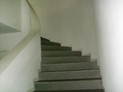 Umwandete Treppe in einem öffentlich zugänglichen Gebäude (Kirchenzentrum) ohne Handlauf.